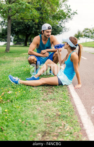 Young couple working out, taking a break - Stock Photo