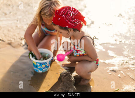 Two little girls playing together on the beach - Stock Photo