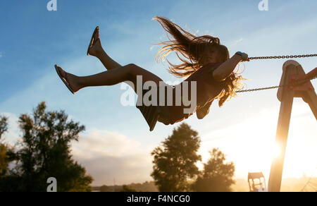 Girl with blowing hair on a swing at backlight - Stock Photo