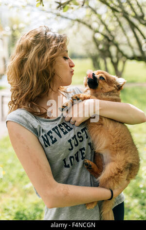 Young woman cuddling with a Pomeranian puppy - Stock Photo