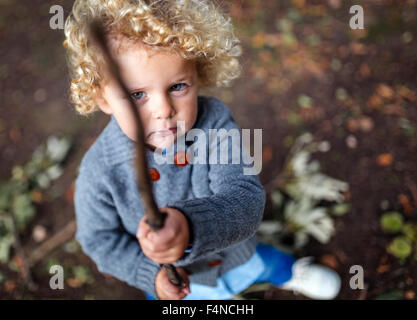 Portrait of little boy holding a stick - Stock Photo