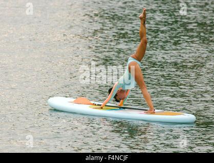 Woman practicing paddle board yoga - Stock Photo
