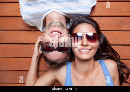 Happy young couple lying head to head on a wooden floor - Stock Photo