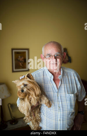 Portrait of smiling senior man  holding his Yorkshire Terrier - Stock Photo