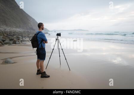 Spain, Valdovino, photographer standing on the beach taking photos with a tripod - Stock Photo