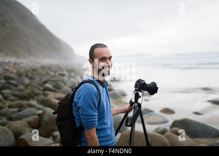 Spain, Valdovino, portrait of smiling photographer on the beach with tripod and camera - Stock Photo