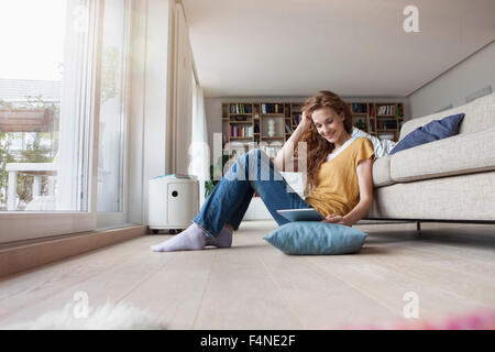 Woman at home sitting on floor holding digital tablet - Stock Photo