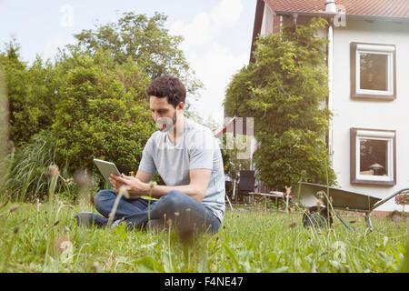 Man sitting in garden using digital tablet - Stock Photo