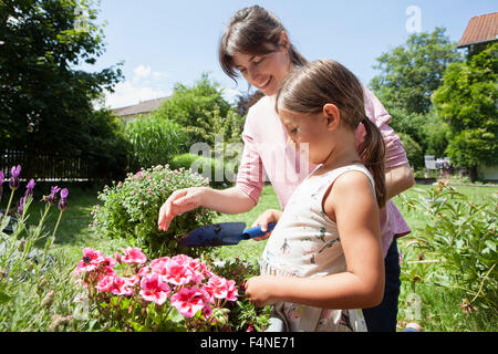Smiling mother and daughter in garden planting flowers - Stock Photo