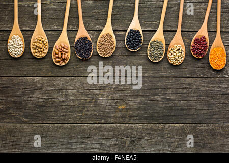 various dried legumes in wooden spoons on old table - Stock Photo
