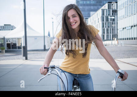 Germany, Cologne, portrait of smiling young woman with blowing hair on her bicycle - Stock Photo