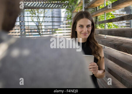 Smiling young woman with digital tablet in pergola - Stock Photo