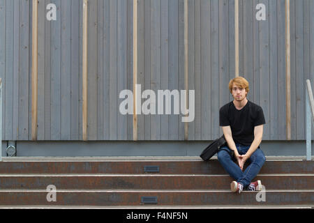 Young man sitting on steps in front of wooden facade - Stock Photo