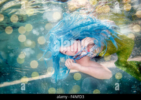 Young woman in the disguise of Arielle, the little mermaid, blue hair, underwater - Stock Photo