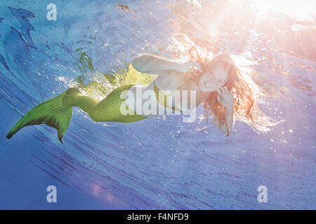 Young woman in the disguise of Arielle, the little mermaid, underwater - Stock Photo