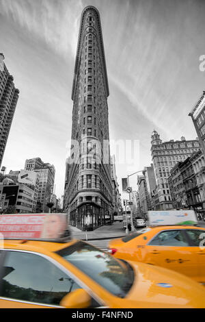 Selective colour image of the iconic Flatiron Building with two yellow cabs, Manhattan New York USA - Stock Photo
