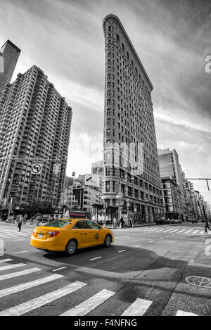 Selective colour image of the iconic Flatiron Building with a yellow cab, Manhattan New York USA - Stock Photo