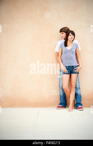 Portrait of young couple leaning against wall - Stock Photo