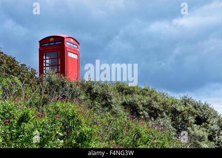 Old red telephone box in South Devon, taken near Challaborough, UK - Stock Photo