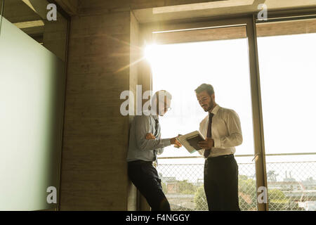 Two young businessmen talking at the window in office - Stock Photo