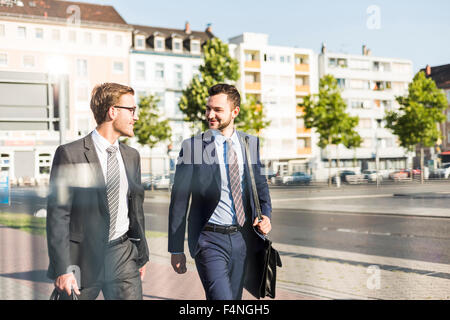 Two young businessmen walking in city - Stock Photo