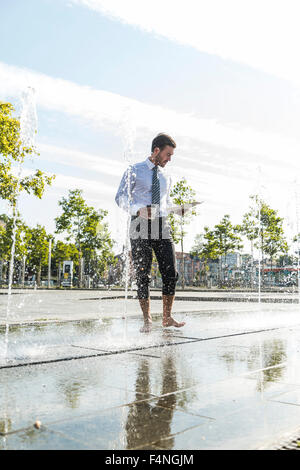 Young businessman standing in fountain, reading documents - Stock Photo