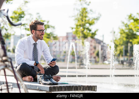 Young businessman sitting cross-legged on bench, using smartphone - Stock Photo