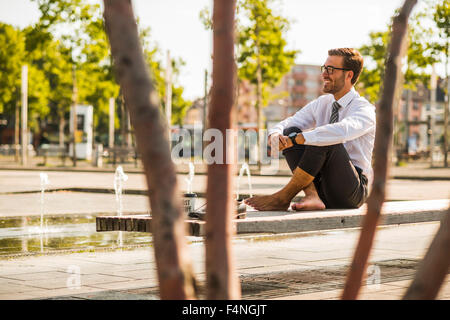 Young businessman sitting cross-legged on bench - Stock Photo