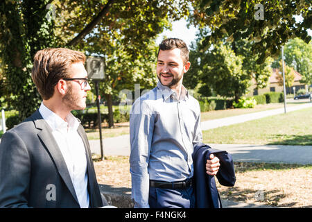 Two young businessmen walking together - Stock Photo