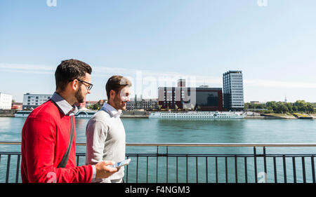 Two young businessmen walking by the riverside - Stock Photo