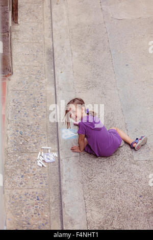 Smiling girl drawing with crayon on the street - Stock Photo
