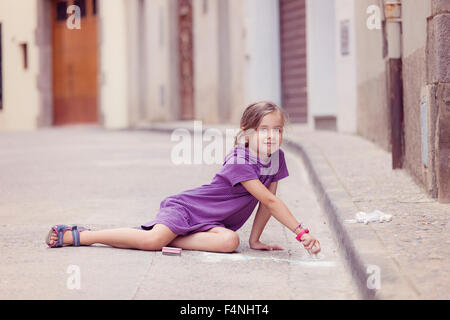 Little girl drawing with crayon on the street - Stock Photo