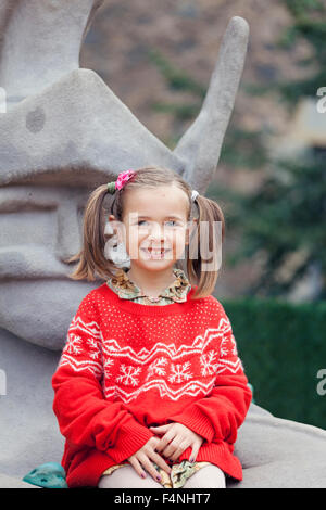 Portrait of a smiling little girl with braids wearing red-white knit pullover - Stock Photo