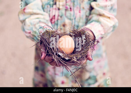 Girl holding an egg in a nest - Stock Photo