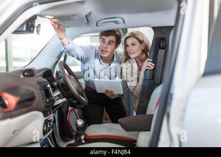 Car dealer showing new car to woman - Stock Photo