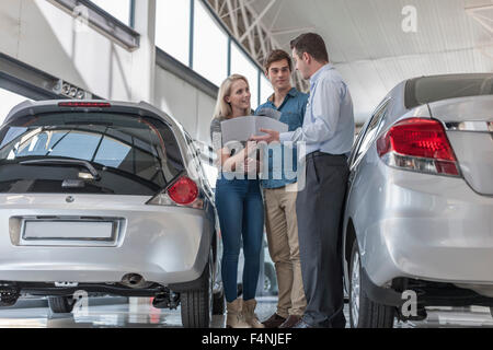 Car dealer showing brochure to young couple in showroom - Stock Photo