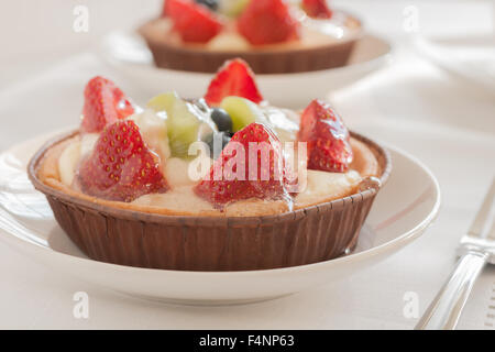 Fruit tarts made filled with creme patissiere strawberries kiwi fruit and blueberries - Stock Photo