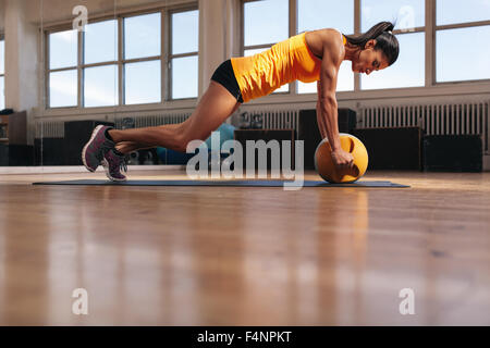 Fit young female athlete working out on her core muscles. Muscular woman exercising on fitness mat doing push ups - Stock Photo