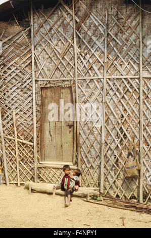 Nagaland, India - March 2012: Small children sitting in front of traditional house in Nagaland, remote region of - Stock Photo