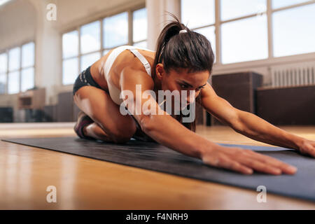 Young muscular woman doing stretching workout on fitness mat. Female performing yoga at gym. - Stock Photo