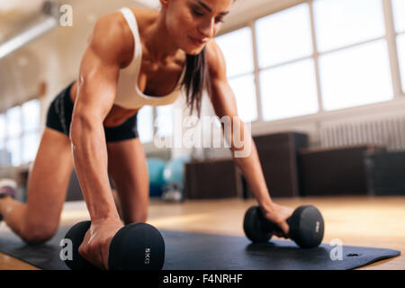 Woman doing push-ups on dumbbells at the gym, focus of arms of woman. - Stock Photo
