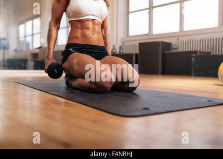 Cropped image of muscular woman exercising with dumbbells while sitting on fitness mat in gym. Focus on abs. - Stock Photo