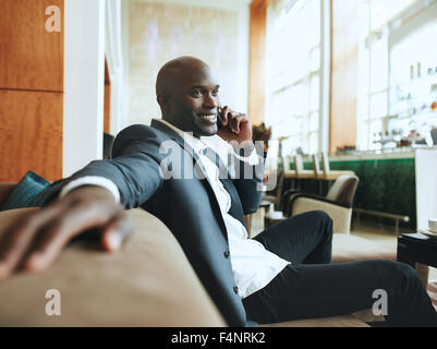 Happy young businessman sitting relaxed on sofa at hotel lobby making a phone call, waiting for someone. - Stock Photo