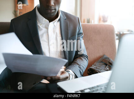 Cropped shot of young businessman going through some paperwork. African business executive reading documents while - Stock Photo