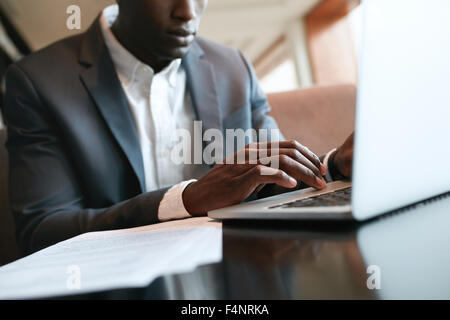 Close up shot of male hands typing on laptop keyboard. African businessman working on laptop computer at cafe. - Stock Photo