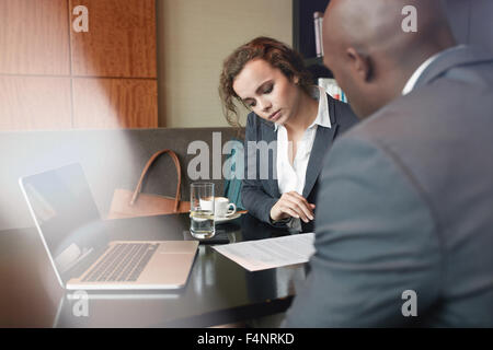 Serious business people working together in a cafe and reading some contract documents. Businessman and businesswoman - Stock Photo