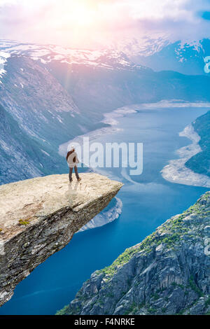 Woman On Trolltunga -  View On Norway Mountain Landscape From Trolltunga - The Troll's tongue in Odda, Ringedalsvatnet - Stock Photo