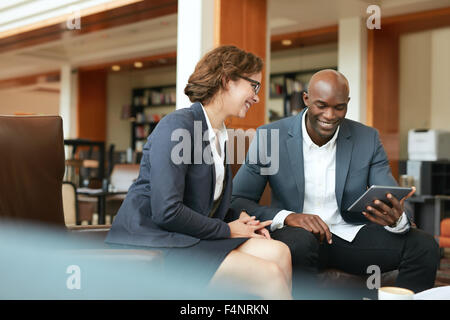 Shot of two people looking at something on a touchscreen computer. Smiling business people using digital tablet - Stock Photo