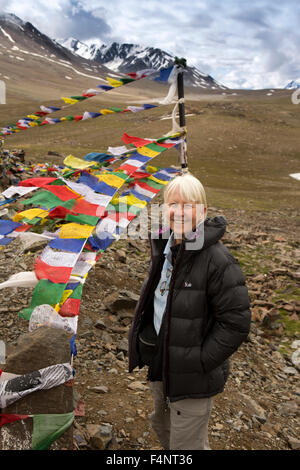 India, Himachal Pradesh, Baralacha Pass top, senior woman tourist Buddhist prayer flags at summit - Stock Photo