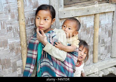 Nagaland, India - March 2012: Small girl with younger brother and sister in Nagaland, remote region of India. Documentary - Stock Photo